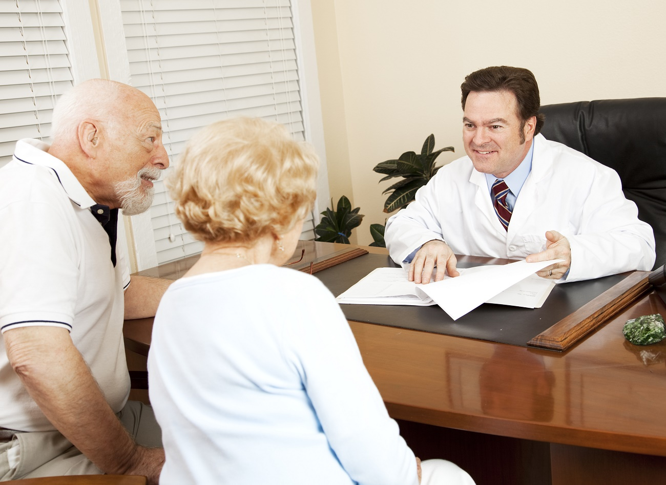 Doctor reviews the medical test results of a senior couple and gives them the good news.