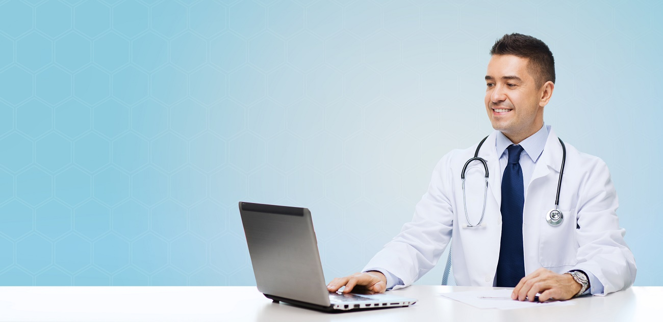 medicine, profession, technology and people concept - smiling male doctor sitting at table with laptop and stethoscope over blue background