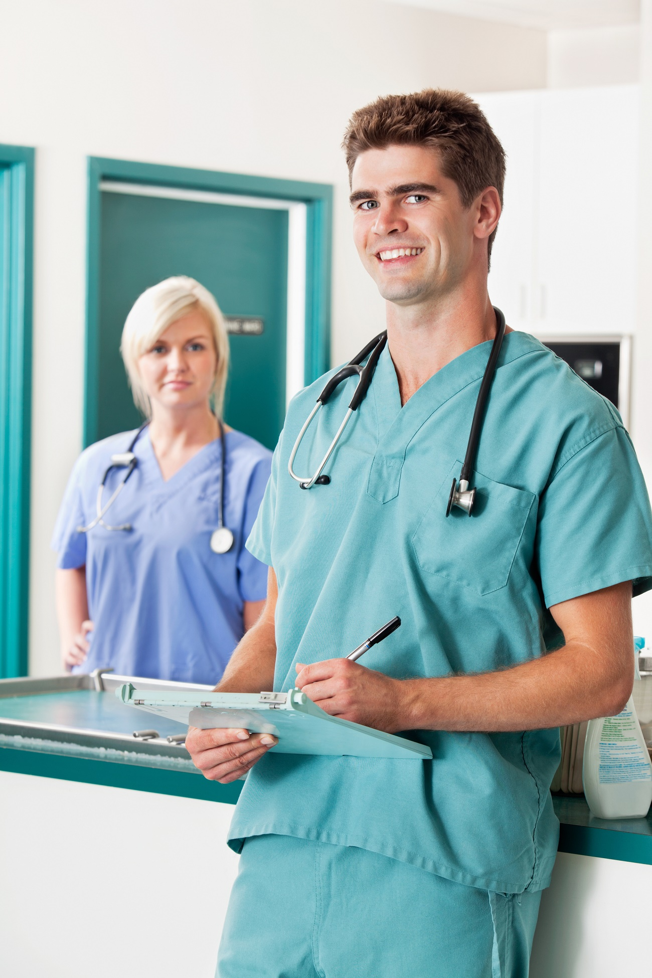 Portrait of smiling male veterinarian with clipboard while assistant in the background